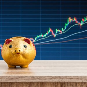 a piggybank in front of a stock market chart